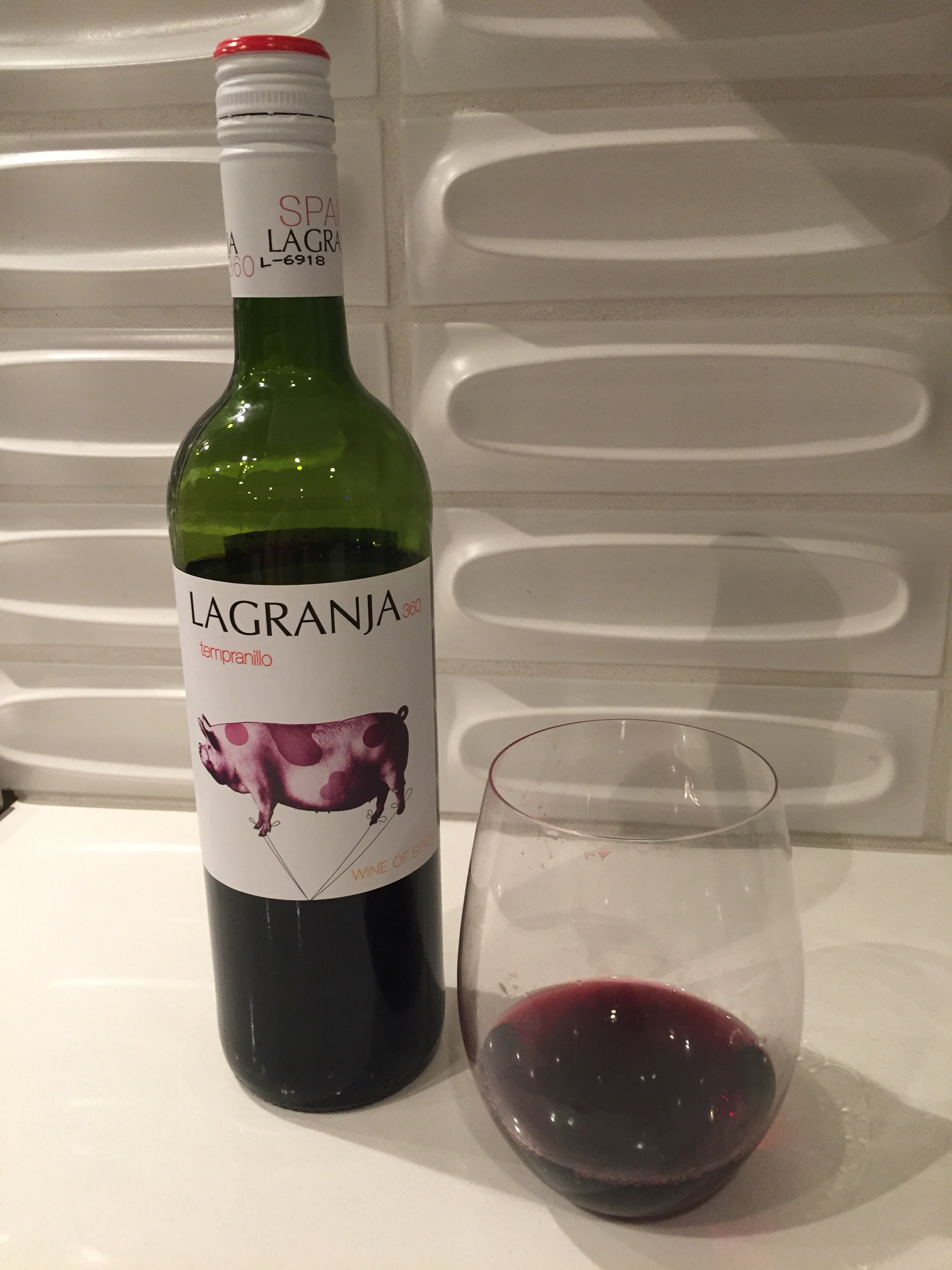 Glass and bottle of La Granja 360 Tempranillo from Trader Joe's