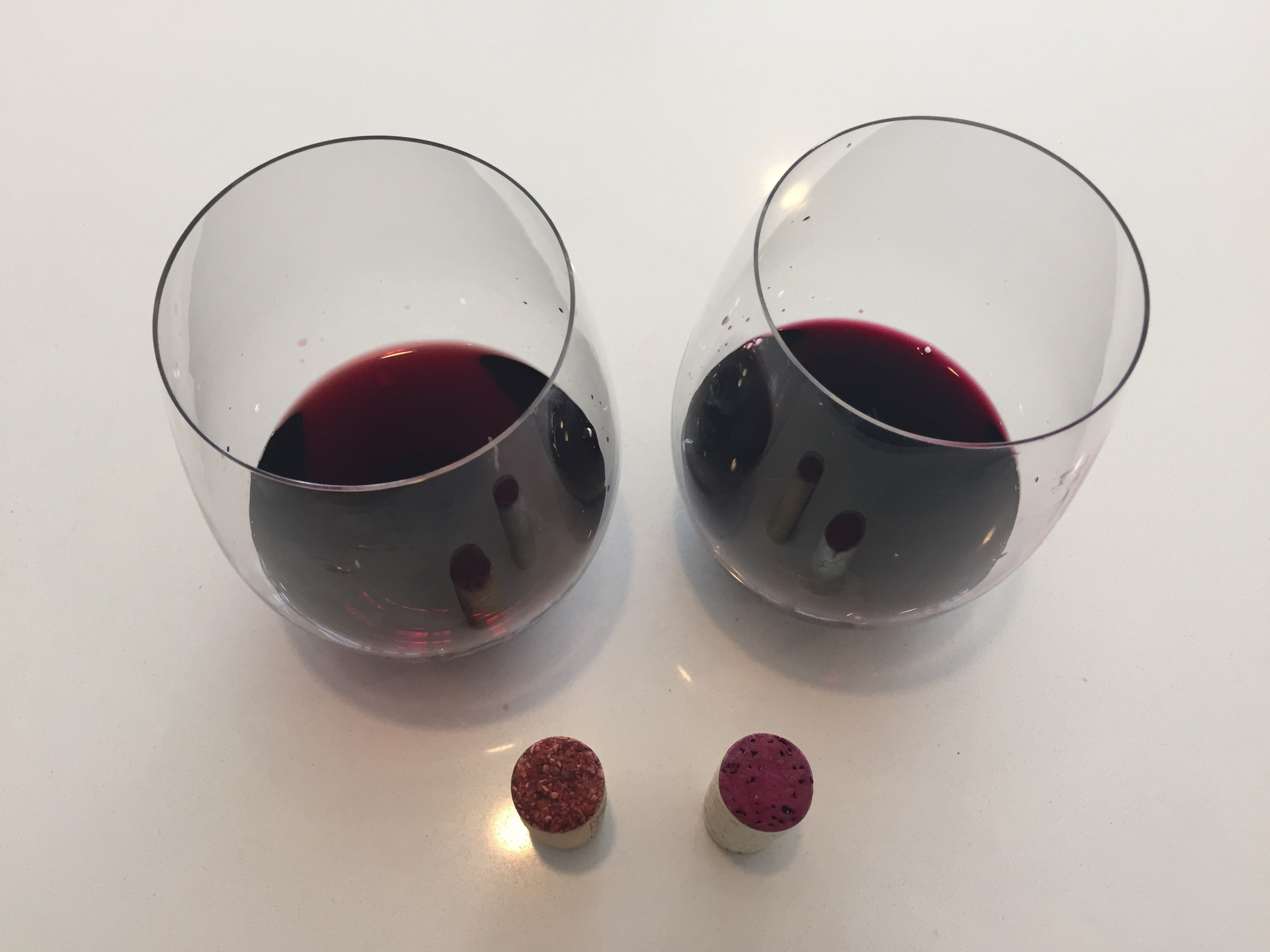 A glass of the brick red 2016 Kirkland Signature on the left, and a glass of the electric red/purple 2017 TJ's Reserve on the right.
