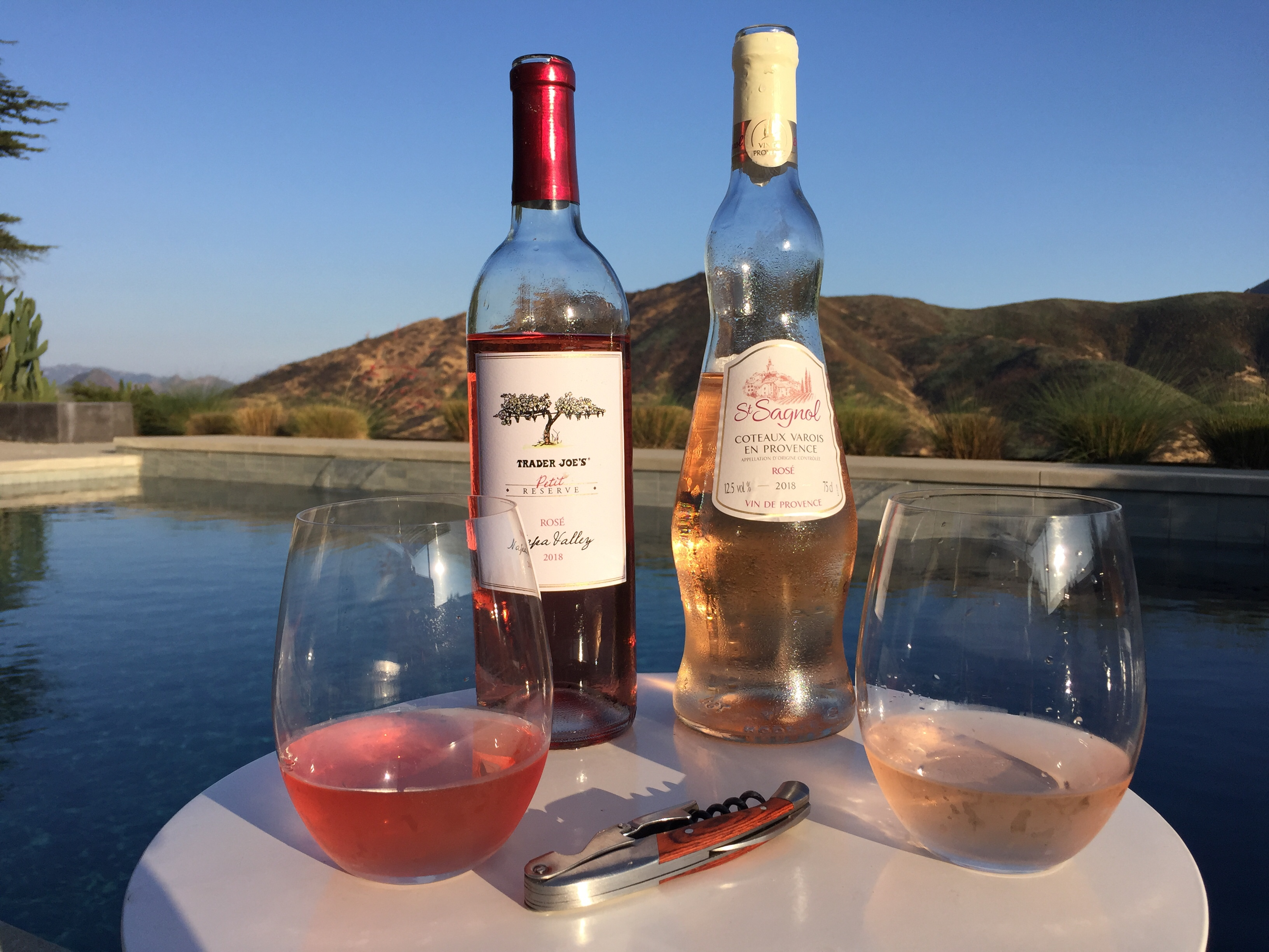 Photo of two bottles and glasses of rose from Trader Joe's, one from California, the other from France