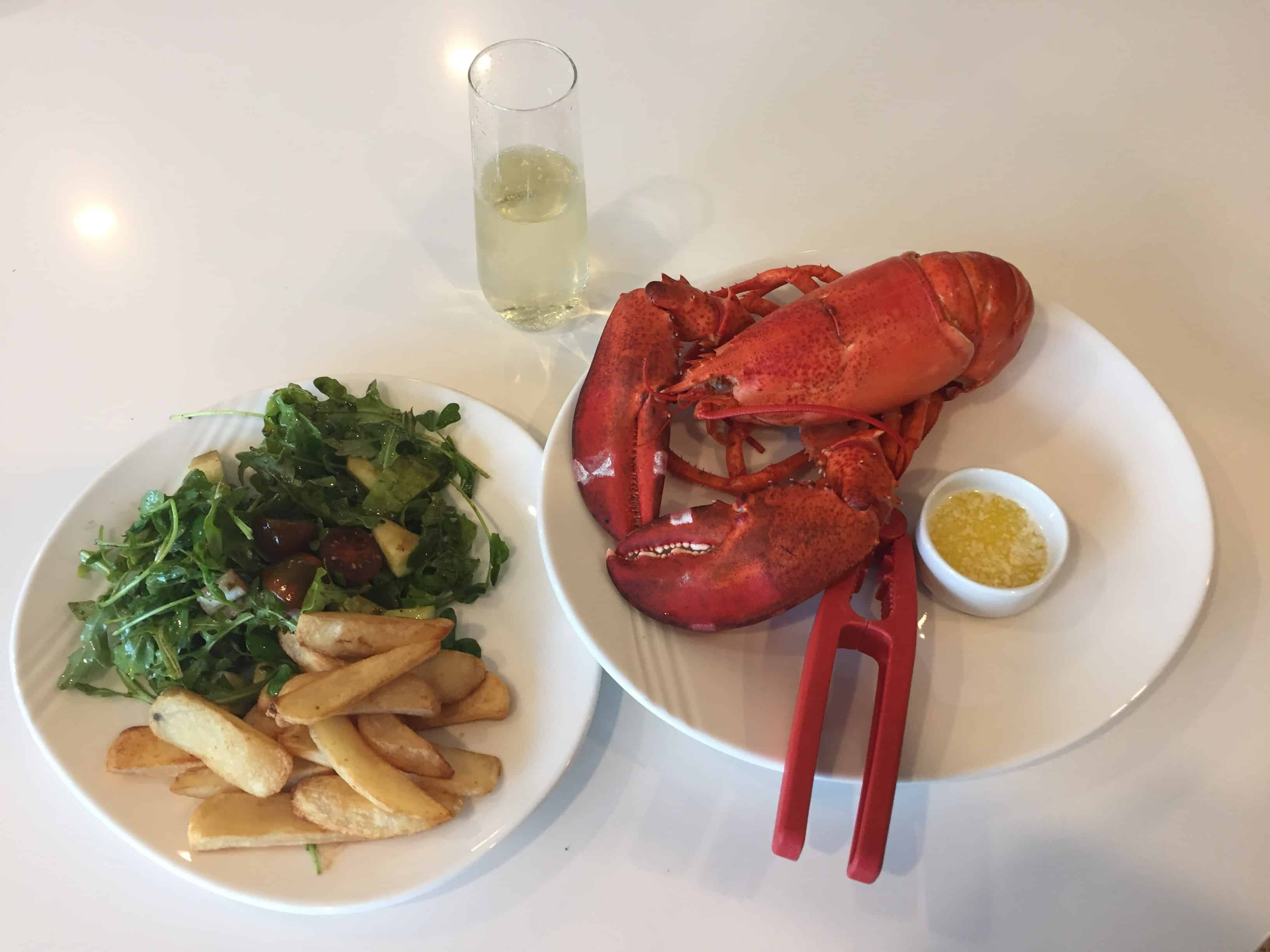 Photo of cooked lobster on a plate with french fries and a glass of wine.