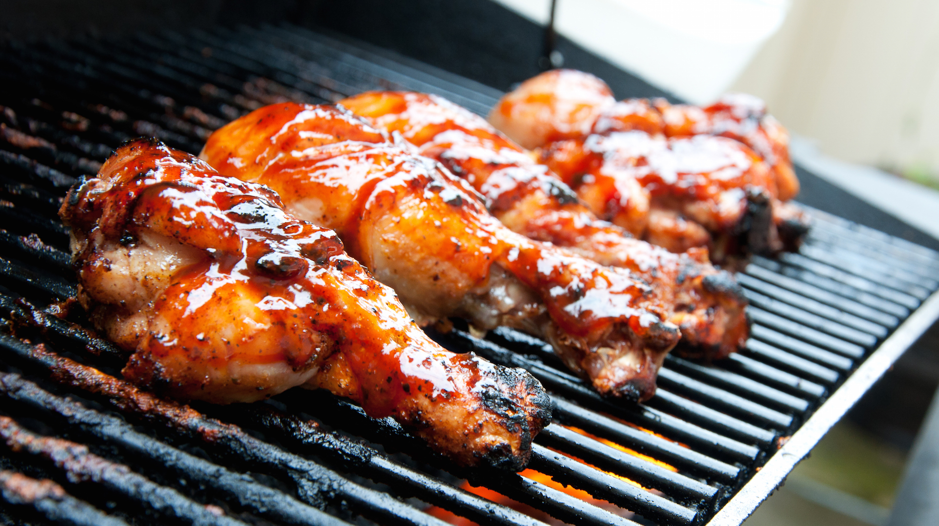 Chicken barbecuing on a gas grill.