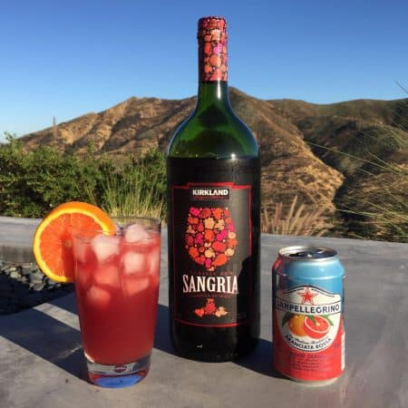 Photo of bottle of Kirkland Signature Sangria, a can of San Pellegrino Blood Orange Soda and a glass with the two combined.