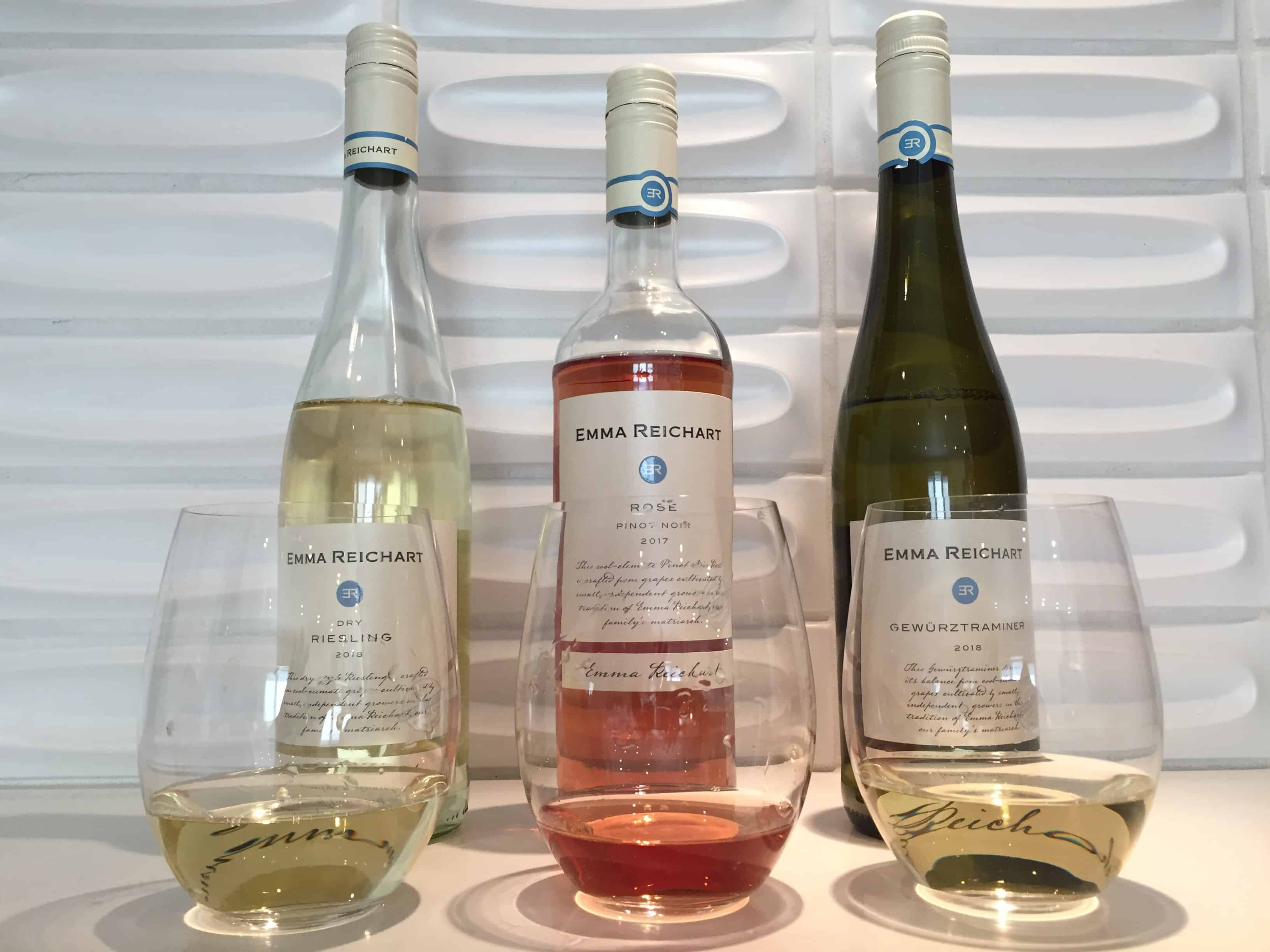 Three glasses and three bottles of wine