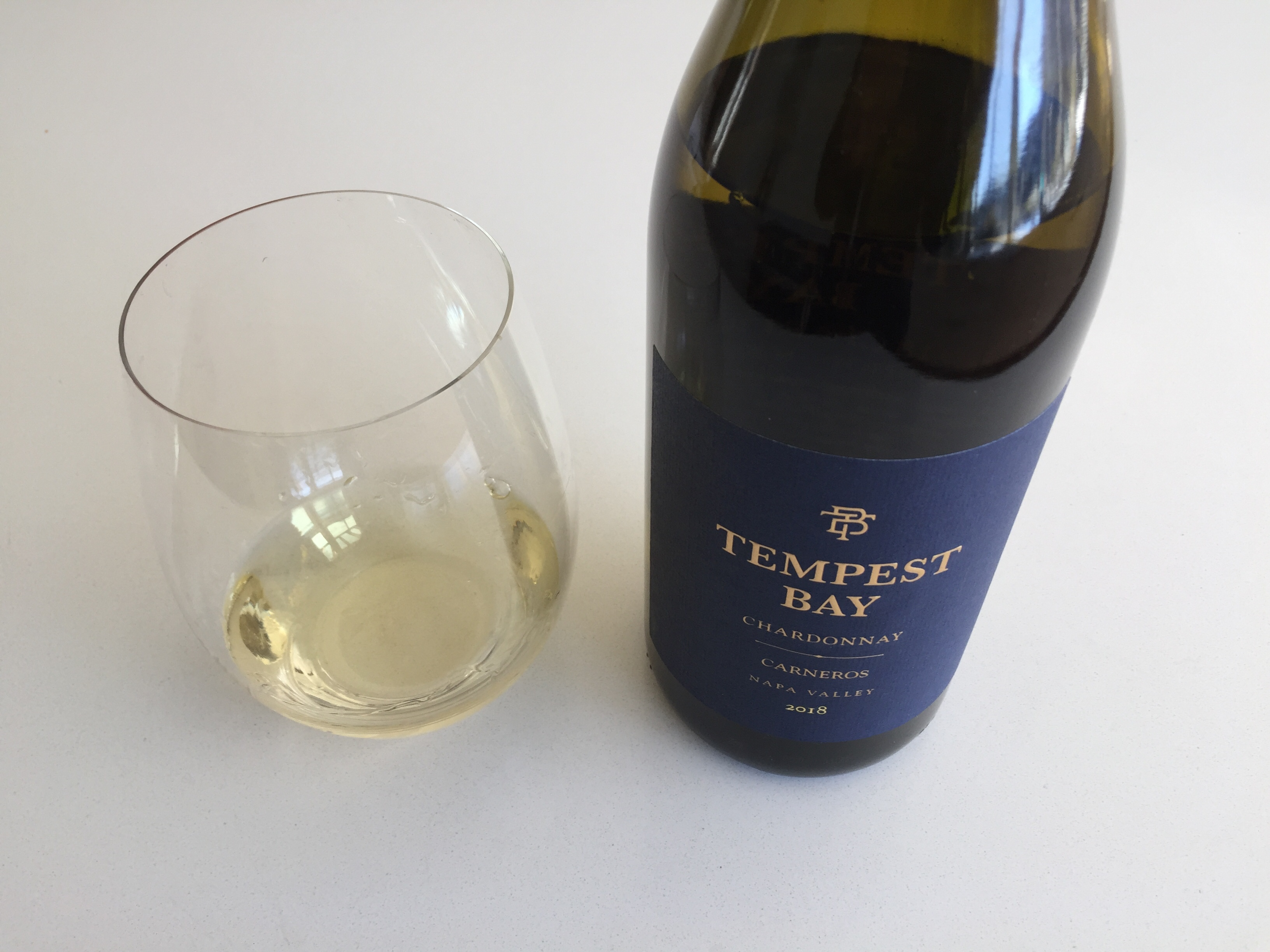Glass and bottle of 2018 Tempest Bay Carneros Chardonnay from Trader Joe's