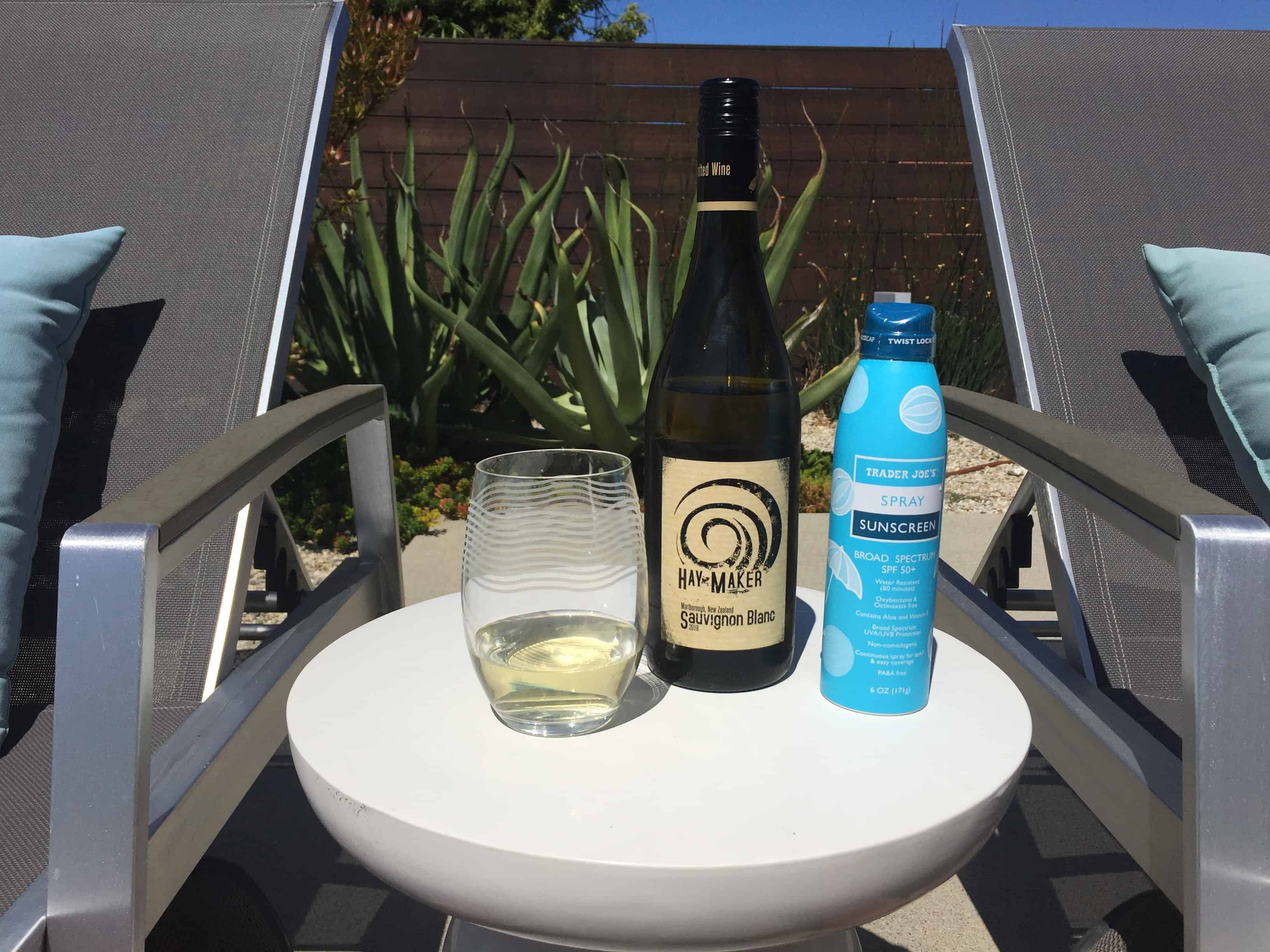 Bottle and glass of Hay Maker New Zealand Sauvignon Blanc from Trader Joe's - with sunscreen spray