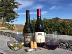 Bottles and glasses of Kirkland Signature Chardonnay and Pinot Noir