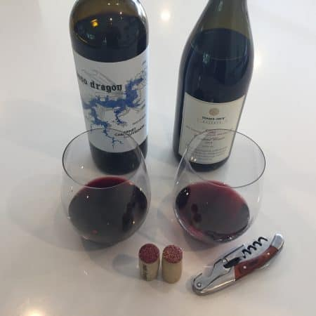 Bottles and glasses of Paso Dragon Cabernet Sauvignon and TJs Reserve GSM. Both 2018 vintage and both from Trader Joe's.