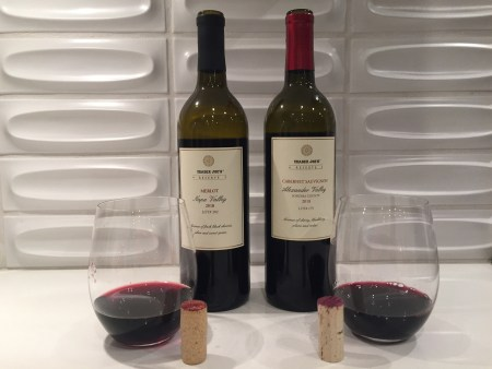 Bottles and glasses of Trader Joe's Reserve 2018 Merlot Lot #202 (left) and 2018 Cabernet Sauvignon Lot #179