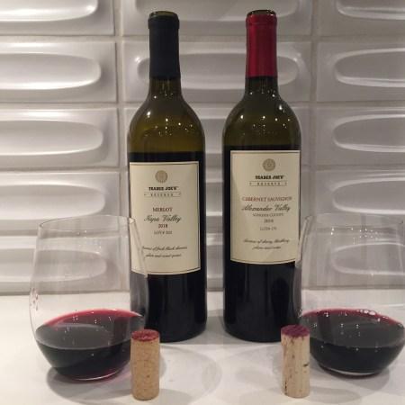 Bottles and glasses of Trader Joe's Reserve 2018 Merlot Lot #202 (left) and 2018 Cabernet Sauvignon Lot #179