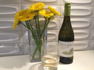 Bottle and glass of Pine Ridge 2020 Chenin Blanc + Viognier - and a vase of yellow Gerberra Daisies