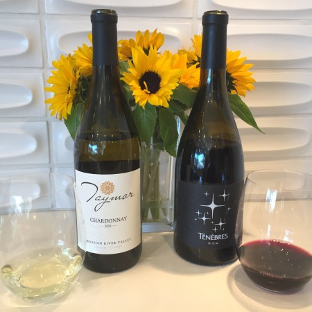 Bottles and glasses of Taymor Chardonnay (left) and Tenebres GSM - both from Trader Joe's, and both $4.99