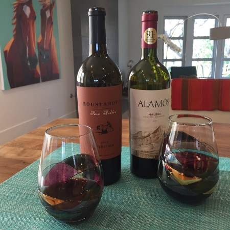 Bottles and glasses of Roustabout Meritage and Alamos Malbec from Trader Joe's