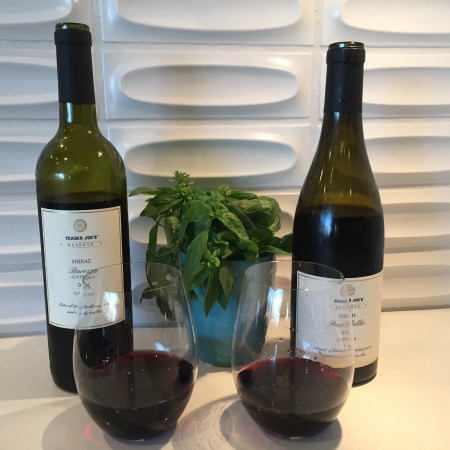 Bottles and glasses of Trader Joe's Reserve 2018 Syrah from Paso Robles, California and 2018 Shiraz from Barossa, Australia - both $9.99 at TJ's