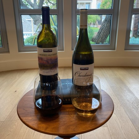 Glasses and bottles of Kirkland Signature 2019 Russian River Valley (Sonoma County) Chardonnay and Kirkland Signature 2019 Columbia Valley (Washington State) Cabernet Sauvignon