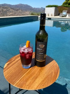 Bottle and glass of Stella Rosa Black, poolside