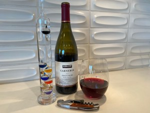 Bottle and glass of Kirkland Signature 2019 Carneros Pinot Noir from Costco.