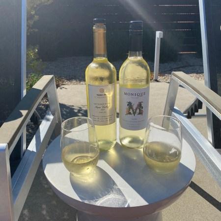 Bottles and glasses of Trader Joe's Reserve Napa 2020 Sauvignon Blanc (L) and Monique Cellars 2020 Sauvignon Blanc (R)