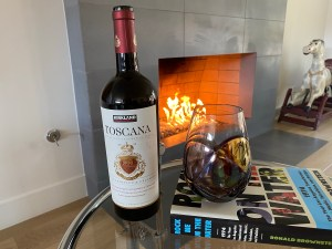 Bottle and glass of Kirkland Signature 2018 Toscana in front of a fire. $14.99 at Costco.