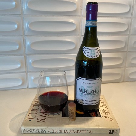 Bottle and glass of 2018 Cecilia Beretta, Valpolicella, Verona, Italy perched atop our all-time favorite cookbook from the chef couple that brought restaurant Al Forno to Providence, Rhode Island.