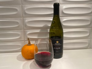 Glass and bottle of 2020 Trader Joe's Grand Reserve Pinot Noir Lot #106, Santa Rita Hills, California - $12.99 in California stores. Oh, and a baby sugar pumpkin that could be a pumpkin tart in a few short weeks!